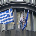 A man adjusts a European flag outside the Greek embassy in Brussels